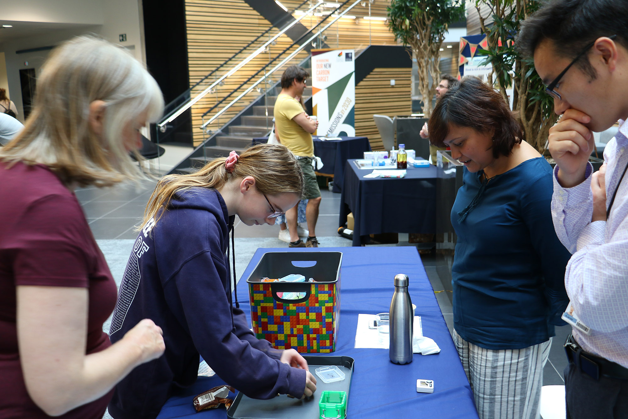 Young girl doing an activity at the 2019 Open Doors event while her mother and 2 researchers watch her.
